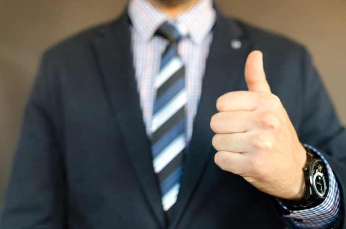 man in suit giving thumbs up sign