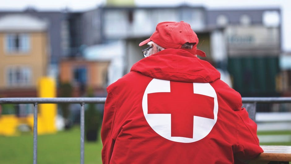 man wearing red cross jacket