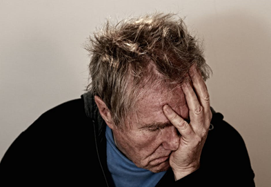 elderly man holding head